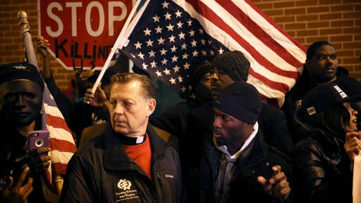 Black Lives Matter activist Jedidah Brown, right,  confers with Father Michael Pfleger Tuesday, Nov. 8, 2016, before a march in the wake of the fatal shooting of Joshua Beal in the Mount Greenwood neighborhood of Chicago. The predominantly white neighborhood on Chicago's southwest side has been rocked by confrontations between protesters and police supporters for the second time since the fatal shooting of a black man by police over the weekend.