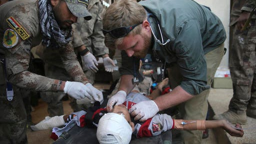 An American volunteer medic, right, and an Iraqi special forces medic, left, treat an injured boy who wounded by a mortar shell in the Zuhur neighborhood, at a field hospital in the Samah front line neighborhood, in Mosul, Iraq, Thursday, Nov. 24, 2016. Iraqi troops on Thursday drove Islamic State militants from three more neighborhoods in the northern city of Mosul, pushing toward the city center in a slow, street-to-street fight that's now in its sixth week, according to a senior Iraqi commander.