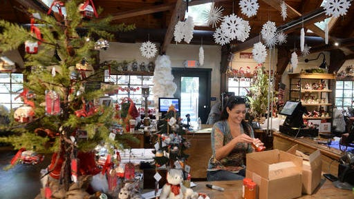 In this Tuesday, Nov. 15, 2016, photo, retail clerk Sarai Kaiser labels merchandise inside the Sky Trading Company Store at the new Skypark at Santa's Village in Skyforest, Calif. Developers have been planning to convert the Christmas-themed 153-acre-park, which has been closed since 1998, into a year-around, action-oriented destination, with mountain biking, fly-fishing, archery, a climbing wall and a zipline.