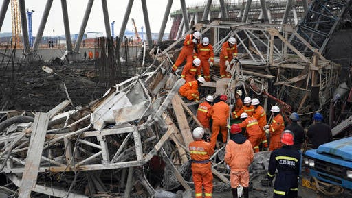 In this photo released by Xinhua News Agency, rescue workers look for survivors after a work platform collapsed at the Fengcheng power plant in eastern China's Jiangxi Province, Nov. 24, 2016. State media reported dozens were killed after the scaffolding tumbled down.