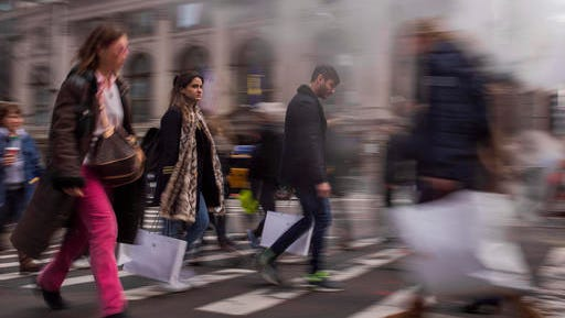 Shoppers carry their purchases as they walk though the steam coming from the underground along Fifth Avenue on Black Friday in New York, Friday, Nov. 25, 2016. Shoppers were on the hunt for deals and were at the stores for entertainment Friday as malls opened for what is still one of the busiest days of the year, even as the start of the holiday season edges ever earlier.