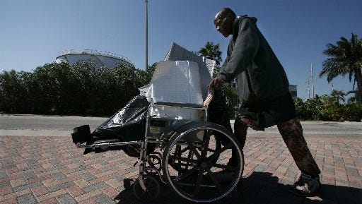 Gregory Gilchrist, 57, a homeless resident of Fort Pierce, pushes a wheelchair holding aluminum debris from Hurricane Wilma while looking for scrap metal for recycling along Indian River Drive in Fort Pierce on Tuesday Oct. 25, 2005.