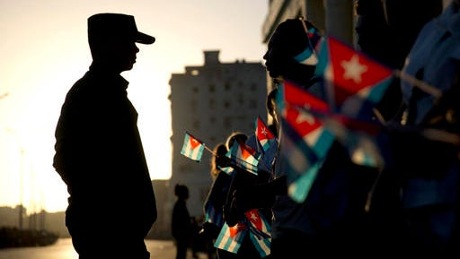 A soldier is silhouetted against the early morning sky as people holding Cuban flags wait for the motorcade transporting the remains of Cuban leader Fidel Castro in Havana, Cuba, Wednesday, Nov. 30, 2016. Castro's ashes have begun a four-day journey across Cuba from Havana to their final resting place in the eastern city of Santiago.