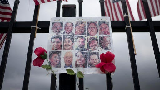 In this Nov. 18, 2016 photo, a faded photo collage showing images of the 14 victims who were killed in the Dec. 2, 2015, San Bernardino terror attack is adorned with artificial flowers at a makeshift memorial near the Inland Regional Center in San Bernardino, Calif., where the shooting took place. Last December, San Bernardino County health inspector Syed Farook and his Pakistan-born wife Tashfeen Malik opened fire on a meeting of Farook's colleagues, and were killed in a shootout with police. Investigators said the assailants were inspired by the Islamic State group.