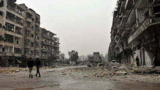This photo released by the Syrian official news agency SANA, shows Syrian troops and pro-government gunmen marching through the streets of east Aleppo, Syria, Tuesday, Dec. 13, 2016. Syrian rebels said Tuesday that they reached a cease-fire deal with Moscow to evacuate civilians and fighters from eastern Aleppo, after the U.N. and opposition activists reported possible mass killings by government forces closing in on the rebels' last enclave.