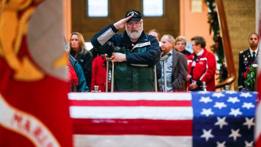 A mourner salutes the casket of John Glenn as he lies in honor, Friday, Dec. 16, 2016, in Columbus, Ohio. Glenn's home state and the nation began saying goodbye to the famed astronaut who died last week at the age of 95.