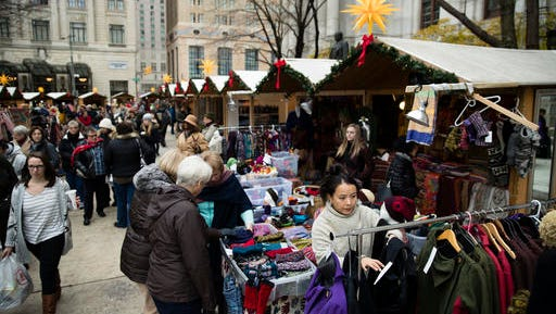 In this Thursday, Dec. 8, 2016, photo, shoppers look for gifts in booths set up for the holidays around City Hall in Philadelphia. New numbers from a key data source show that shoppers are so far spending at a decent, but slightly slower pace this holiday season compared to last year.
