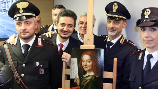 Carabinieri and police officers pose with one of the recovered paintings that were stolen  from a Verona museum, at the Verona airport, Italy, Wednesday, Dec. 21, 2016. Italy's culture minister has traveled to Kiev to recover 17 paintings,  including works by Tintoretto, Rubens and Mantegna, that were stolen from a Verona museum and recovered by Ukrainian law enforcement more than seven months ago. Culture Minister Dario Franceschini and Verona Mayor Flavio Tosi traveled to retrieve the paintings.