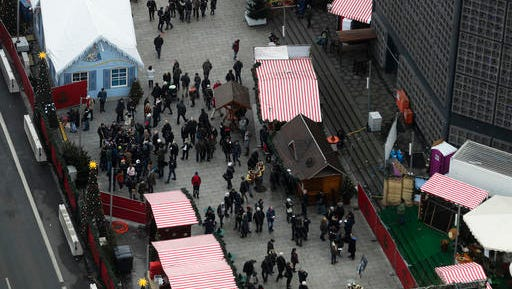 People walk over the reopened Christmas market, three days after a truck ran into the crowd and killed several people, at the Kaiser Wilhelm Memorial Church in Berlin, Thursday, Dec. 22, 2016.