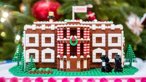 FILE -  In this Tuesday, Nov. 29, 2016 file photo a LEGO model of the White House, one of fifty-six LEGO gingerbread houses, one for each state and territory, is displayed in the trees in the State Dinning Room at the White House during a preview of the 2016 holiday decor, in Washington. White House holiday displays were created this year by Lego's master builders, a team of seven at the company's US headquarters in Enfield, Conn., who devote hours and tens of thousands of toy bricks to projects that go on display around the world.