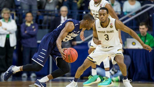 Saint Peter's Chazz Patterson (20) drives in front of Notre Dame's V.J. Beachem (3) during the first half of an NCAA college basketball game Wednesday, Dec. 28, 2016, in South Bend, Ind. (AP Photo/Robert Franklin)