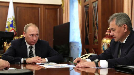 Russian President Vladimir Putin, left, listens to Defence Minister Sergei Shoigu in Moscow, Russia on Thursday, Dec. 29, 2016. Putin is ordering to scale down the Russian military presence in Syria. Putin made the statement Thursday while declaring that a cease-fire in Syria brokered by Russia and Turkey will start at midnight.