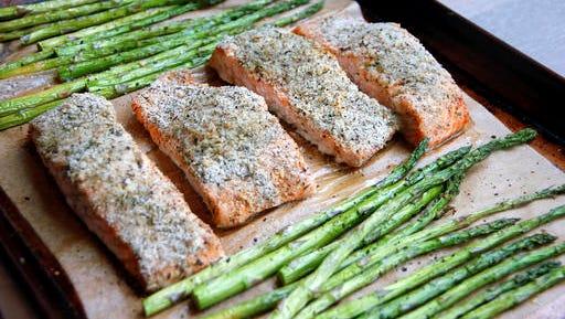 This Jan. 2, 2017 photo shows a sheet-pan supper of salmon and asparagus in Coronado, Calif., a recipe by Melissa d'Arabian.