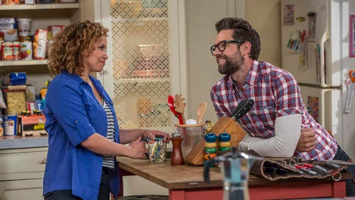 """This image released by Netflix shows Justina Machado, left, and Todd Grinnell in a scene from """"One Day At A Time."""" The series,  a remake of the 1970's-80's Norman Lear TV series, centers on a Cuban-American family. It debuts on Netflix on Sunday."""
