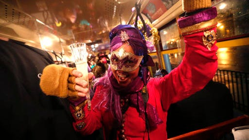 "Cheryl Gerber, a member of the ""Societe des Champs Elysee"" rides the Rampart-St. Claude street car line, which just opened last fall, to commemorate the official start of Mardi Gras season, in New Orleans, Friday, Jan. 6, 2017. Wearing masks and festive costumes, they honored their king and queen at a neighborhood bar and danced as a brass band played ""Carnival Time,"" before boarding their red street car."