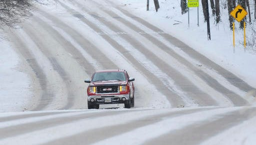 A truck navigates a snowy section of Niles Avenue in St. Joseph, Mich., after a winter weather system dumped several inches of snow in the area, Friday, Jan. 6, 2017.  Michigan transportation officials are urging caution amid wintry weather that's affecting travel across portions of the state.