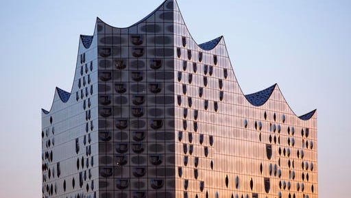 FILE - This Feb. 2, 2016 file picture shows the glass-clad exterior of the Elbe Philharmonic Hall in Hamburg, Germany. Hamburg's spectacular new Elbphilharmonie concert hall is to finally host its first concert on Wednesday  Jan. 11, 2017 night, several years behind schedule and far over the original budget. Germany's President Joachim Gauck and Chancellor Angela Merkel are among the guests expected at the maiden concert, to be conducted by Thomas Hengelbrock. The NDR Elbphilharmonie Orchester will present a mélange of compositions from the renaissance to the present.