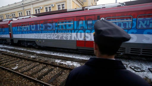 "A railroad worker stands by the first train decorated with letters that read ""Kosovo is Serbian"" written in twenty languages departing from the Belgrade to Mitrovica, Kosovo at Belgrade's railway station, Serbia, Saturday, Jan. 14, 2017. Serbia has launched a railway link to Serb-dominated northern Kosovo despite protests from authorities in Pristina who described the move as a provocation and an aggressive violation of Kosovo's sovereignty."