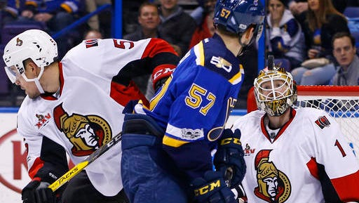 Ottawa Senators goalie Mike Condon, right, keeps his eye on a deflected puck as Cody Ceci, left, and St. Louis Blues' David Perron look for the rebound during the second period of an NHL hockey game, Tuesday, Jan. 17, 2017, in St. Louis. (AP Photo/Billy Hurst)