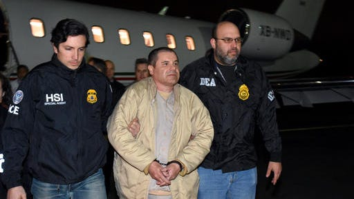 "In this photo provided U.S. law enforcement, authorities escort Joaquin ""El Chapo"" Guzman, center, from a plane to a waiting caravan of SUVs at Long Island MacArthur Airport on Thursday, Jan. 19, 2017, in Ronkonkoma, N.Y. The infamous drug kingpin who twice escaped from maximum-security prisons in Mexico was extradited at the request of the U.S. to face drug trafficking and other charges, and landed in New York late Thursday, a federal law enforcement official said."
