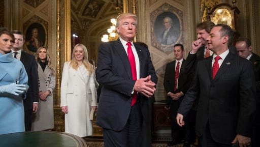 President Donald Trump leaves the President's Room of the Senate on Capitol Hill in Washington, Friday, Jan. 20, 2107, after he formally signed his cabinet nominations into law. He is joined at far left by his wife, first lady Melania Trump and daughter Tiffany Trump. At far right is Chief of Staff Reince Priebus, with White House counsel Donald McGahn, second from right.