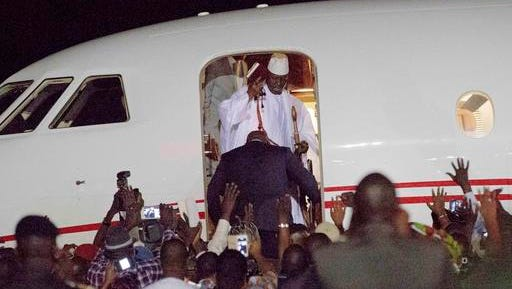 Gambia's defeated leader Yahya Jammeh waves to supporters as he departs at Banjul airport Saturday Jan. 21, 2017. Jammeh announced early Saturday he has decided to relinquish power, after hours of last-ditch talks with regional leaders and the threat by a regional military force to make him leave.