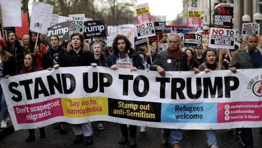 People hold a banner as they take part in a protest march in London, against U.S. President Donald Trump's ban on travellers and immigrants from seven predominantly Muslim countries entering the U.S., Saturday, Feb. 4, 2017. Thousands of protesters have marched on Parliament in London to demand that the British government withdraw its invitation to U.S. President Donald Trump.