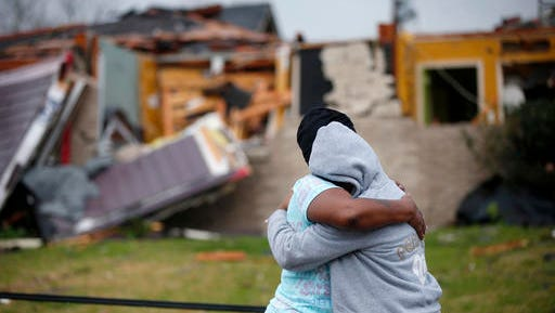Lisa Carruth hugs her granddaughter Juayonna Carruth after a tornado tore through the New Orleans East neighborhood in New Orleans, Tuesday, Feb. 7, 2017.
