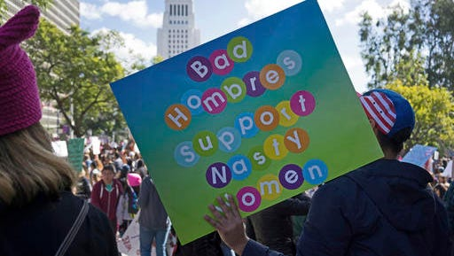 """Andy Solano, holds a sign stating, """"Bad hombres support nasty women,"""" at a rally in downtown Los Angeles Saturday, Jan. 21, 2017. Tens of thousands of demonstrators filled Los Angeles streets with signs decrying President Donald Trump and chants in English and Spanish as a cross-section of the city's diverse religious, ethnic and LGBT groups marched in solidarity Saturday with the Women's March on Washington."""