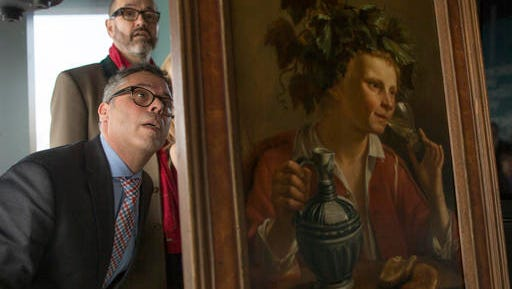 """Dr. Clarence Epstein, foreground, director of the Max Stern Art Restitution Project, inspects the back of """"Young Man As Bacchus"""" by Jan Franse Verzijl during a ceremony to formally return the painting to representatives of the Max and Iris Stern Foundation, Wednesday, Feb. 8, 2017, at the Museum of Jewish Heritage in New York. Federal investigators recovered the 1630 oil painting in a 2015 art fair."""