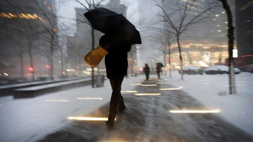 A man makes his way through wind and snow in New York's Zuccotti Park, Thursday, Feb. 9, 2017. A powerful, fast-moving storm swept through the northeastern U.S. Thursday, making for a slippery morning commute and leaving some residents bracing for blizzard conditions.