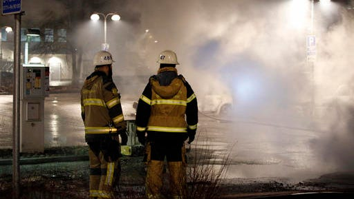 In this picture taken on Monday, Feb. 20, 2017, firefighters survey the scene in the suburb of Rinkeby outside Stockholm. Police in Sweden said Tuesday they were investigating riots that broke out overnight in a predominantly immigrant Stockholm suburb after officers arrested a suspect on drug charges. Spokesman Lars Bystrom said unidentified people, including some wearing masks, threw rocks at police, set cars on fire and looted shops in Rinkeby, north of Stockholm.