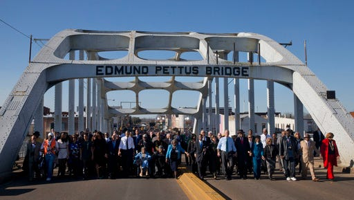 """FILE - In this March 7, 2015, file photo, President Barack Obama, first lady Michelle Obama, their daughters Malia and Sasha, as well as members of Congress, former President George W. Bush, and civil rights leaders make a symbolic walk across the Edmund Pettus Bridge in Selma, Ala., on the 50th anniversary of """"Bloody Sunday,"""" a civil rights march in which protestors were beaten, trampled and tear-gassed by police at the site. Blacks who celebrate the civil rights movement and whites who commemorate the Civil War are suddenly finding themselves fighting on the same side in historic Selma, Alabama: against City Hall."""