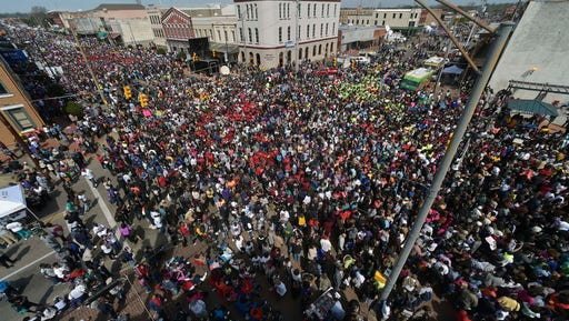 FILE- In this March 8, 2015, file photo, crowds gather before a symbolic walk across the Edmund Pettus Bridge in Selma, Ala. Organizers of the annual civil rights celebration and organizers of a Civil War battle re-enactment are upset the city is asking them to pay tens of thousands of dollars to cover the costs of police and fire protection and cleanup. (AP Photo/Mike Stewart, File)