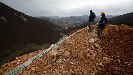 Workers survey damage after a landslide near the Bosnian town of Kakanj located 50 kms north of Sarajevo on Friday, Feb. 24, 2017. More than 150 people have been forced to evacuate their homes in central Bosnia due to a major landslide at an open pit coal mine that threatened to bury their villages.