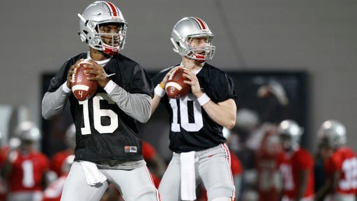 Ohio State quarterbacks J.T. Barrett, left, and Joe Burrow drop back to pass during spring NCAA college football practice Tuesday, March 7, 2017, in Columbus, Ohio. (AP Photo/Jay LaPrete)