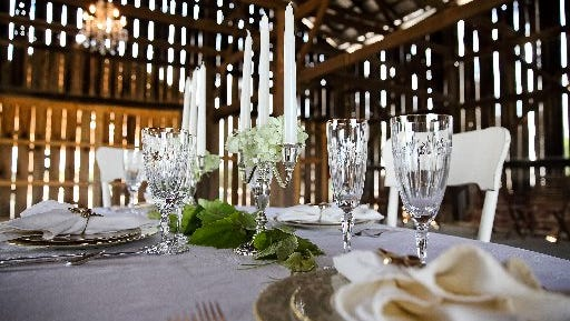 A table is set in the old tobacco barn meeting and event space on the property of Farmer and Frenchman Winery in Henderson County.