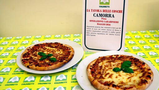 Pizzas are displayed near a sign listing the police operations against restaurants and bars owned by the Camorra crime syndicate, during a report on organized crime infiltration in Italy's much prized food and agriculture businesses at the Coldiretti, the Italian farmers association headquarters in Rome, Tuesday, March 14, 2017. Organized crime has a seemingly insatiable appetite for farm and food businesses, one of the few economic sectors experiencing growth during Italy's protracted economic crisis.