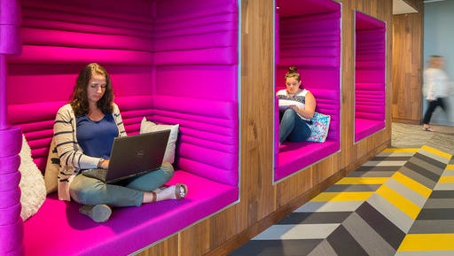 This Aug. 18, 2016 photo shows Jen Taylor and Michelle Bristol of Dyer Brown, an architectural firm, seated in workspaces they designed for the Boston offices of Criteo, a tech company. The comfy cubbies are quiet but bright and cozy. They promote focus and creativity while providing an alternative to a traditional desk or office, and the concept can be adapted for the home.