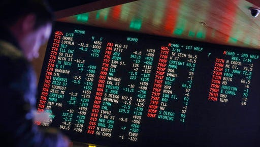 FILE - In this Jan. 14, 2015, file photo, odds are displayed on a screen at a sports book owned and operated by CG Technology in Las Vegas. Las Vegas casinos can't agree on an NCAA tournament favorite, with favorites changing within hours.