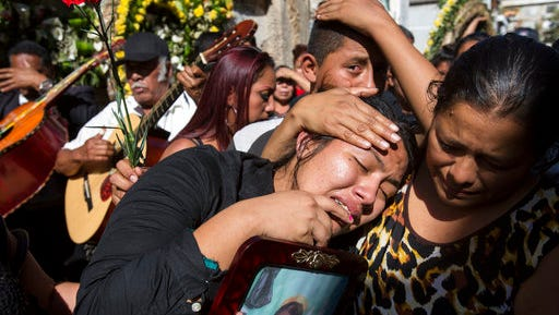 FILE - In this March 17, 2017 file photo, Shirley Palencia weeps during the burial service for 17-year-old sister Kimberly Palencia Ortiz, who died in the Virgen de la Asunción Safe Home fire, at the cemetery in Guatemala City. Authorities said the fire that swept through parts of the institution when mattresses were set ablaze during a protest by girls protesting conditions at the overcrowded youth shelter.