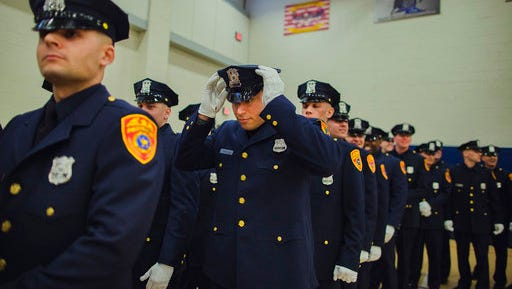 Matias Ferreira, center, adjusts his hat during his graduation ceremony from the Suffolk County Police Department Academy at the Health, Sports and Education Center in Suffolk, Long Island, New York, Friday, March 24, 2017. Ferreira, a former U.S. Marine Corps lance corporal who lost his legs below the knee when he stepped on a hidden explosive in Afghanistan in 2011, is joining a suburban New York police department. The 28-year-old graduated Friday from the Suffolk County Police Academy on Long Island following 29 weeks of training.
