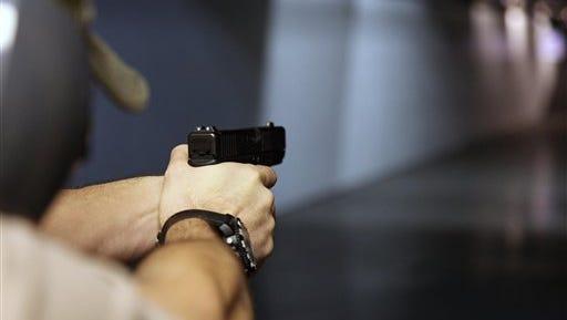 A man fires a hand gun at Sandy Springs Gun Club and Range, in Sandy Springs, Ga.