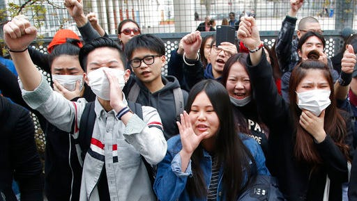 Demonstrators from the Asian community protest outside Paris' 19th district's police station, Tuesday March 28, 2017. Violent clashes in Paris between baton-wielding police and protesters outraged at the police killing of a Chinese man in his home have seen three police officers injured and 35 protesters arrested, authorities said Tuesday.
