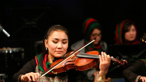 In this Wednesday, Feb. 15, 2017 photo, Zarifa Adiba, 18, an orchestra conductor in Afghanistan, plays during a concert in Kabul. Afghanistan's first all-female symphony is trying to change attitudes in a deeply conservative country where many see music as immoral, especially for women.