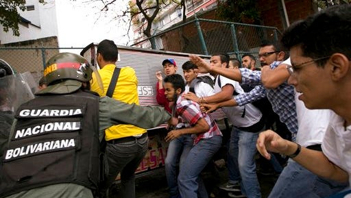 Venezuelan Bolivarian National guards officers are confronted by university students during a protest outside of the Supreme Court in Caracas, Venezuela, Friday, March 31, 2017. Venezuelans have been thrust into a new round of political turbulence after the government-stacked Supreme Court gutted congress of its last vestiges of power, drawing widespread condemnation from foreign governments and sparking protests in the capital.