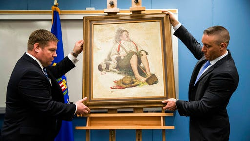 """The Federal Bureau of Investigations Special Agents Don Asper, left, and Jacob Archer displays a recovered Norman Rockwell painting stolen more than 40 years ago, during a news conference at the federal building in Philadelphia, Friday, March 31, 2017. The painting, sometimes called """"Lazybones"""" or """"Boy Asleep with Hoe,"""" graced the cover of the Sept. 6, 1919, edition of the Saturday Evening Post. The oil-on-canvas piece was among several items taken during a 1976 break-in in Cherry Hill, N.J.,  a Philadelphia suburb."""