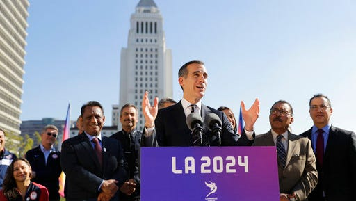 """FILE - In this Jan. 25, 2017, file photo, Los Angeles Mayor Eric Garcetti, center, speaks during a news conference in Los Angeles. More than a million Facebook users """"like"""" the idea of hosting the 2024 Olympic Games in Los Angeles. Mayors from Paris and LA have just flown in to Denmark for an Olympics conference starting Tuesday, April 4, 2017, the first of only three set-piece events between now and September, when the International Olympic Committee is scheduled to pick one city over the other."""