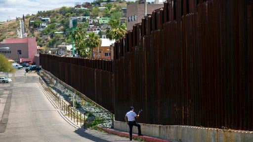 In this April 1, 2017, photo, a man in Nogales, Ariz., talks to his daughter and her mother who are standing on the other side of the border fence in Nogales,
