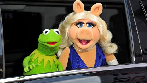 """FILE- In this March 11, 2014, file photo, Kermit the Frog, left, and Miss Piggy arrive at the World Premiere of """"Muppets Most Wanted,"""" in Los Angeles. A New York City museum is asking fans of Jim Henson's Muppets to help pay for an exhibition featuring original puppets of beloved characters like Elmo, Miss Piggy and Kermit the Frog. The Museum of the Moving Image launched a Kickstarter campaign Tuesday, April 11, 2017, seeking $40,000 to help preserve the puppets for posterity."""